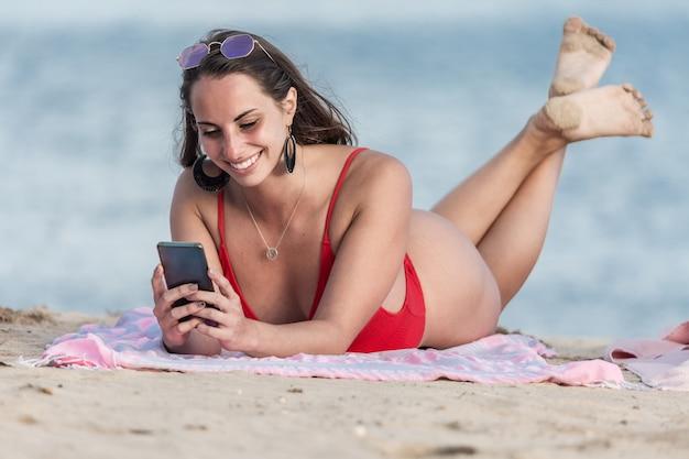 Mujer descalza navegación smartphone en la playa