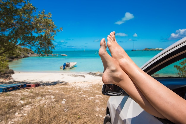 Mujer descalza desde la ventana de un automóvil en playa tropical
