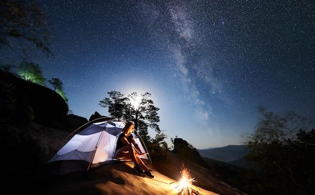 Mujer descansando al lado del campamento, fogata y carpa turística en la noche