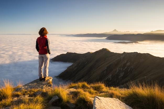 Mujer descansando en la cima de la montaña