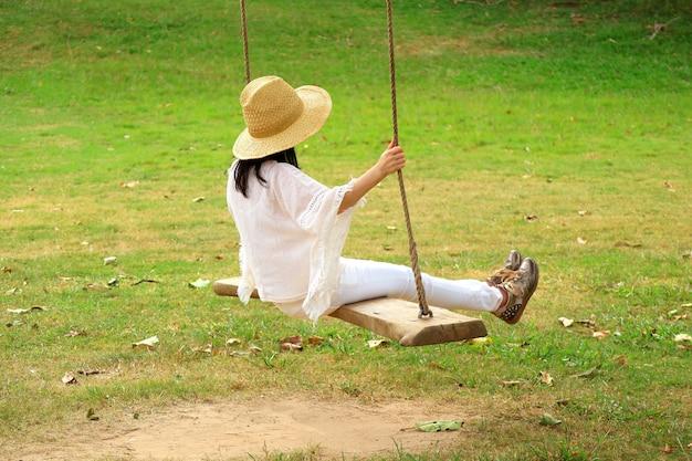Mujer descansando en un columpio de madera en el parque