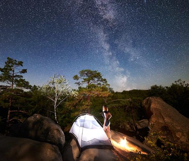 Mujer descansando junto al campamento, fogata y carpa turística en la noche