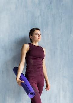 Mujer descansando junto a la pared mientras sostiene una estera de yoga