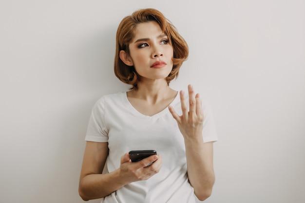 Mujer descansando y relajarse en la habitación con su teléfono inteligente en la mano