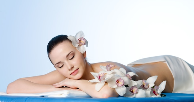 Mujer descansando en el salón de belleza spa con flores - espacio de color