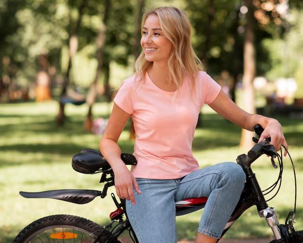 Mujer descansando sobre bicicleta y apartar la mirada
