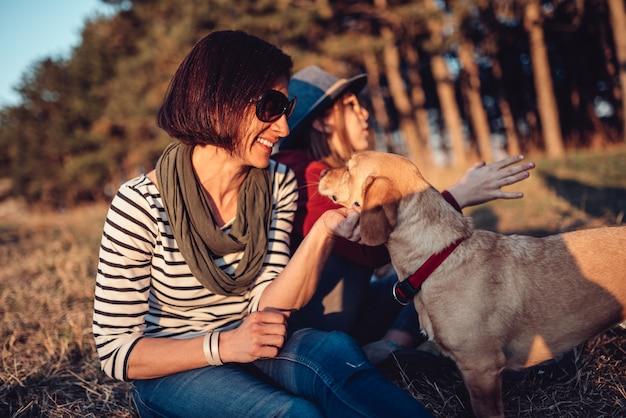 Mujer descansando sobre el césped con la familia y abrazando a su perro