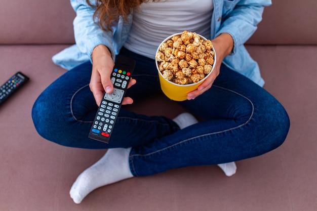 Mujer descansando en el sofá y comiendo palomitas crujientes de caramelo mientras mira televisión
