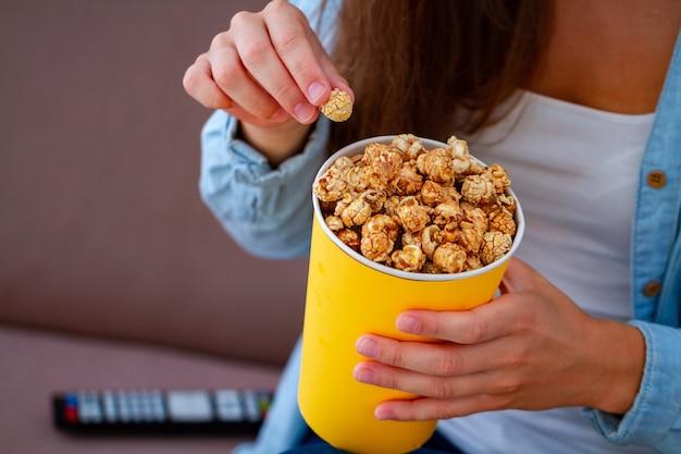 Mujer descansando en el sofá y sosteniendo la caja de palomitas crujientes de caramelo para la merienda durante la televisión en casa. película de palomitas de maíz