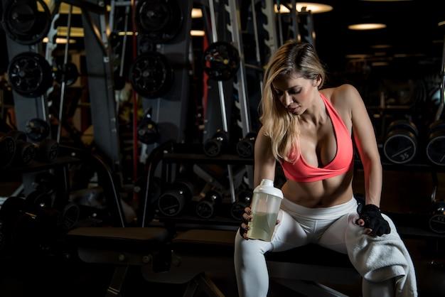 Mujer descansando sudando con una toalla y agua potable en el gimnasio.