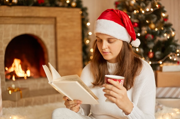 Mujer descansando con una taza de bebida caliente y un libro junto a la chimenea y el árbol de navidad, mirando concentrado en las páginas, pasando el tiempo libre, vistiendo un sombrero festivo y un suéter de punto blanco.
