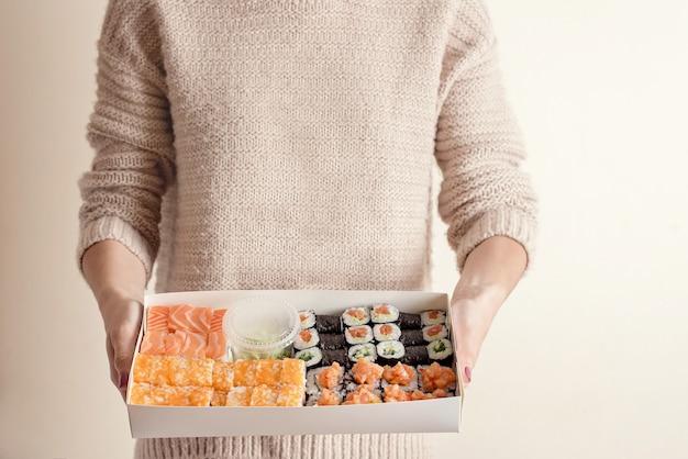 Mujer desconocida que sostiene el conjunto de comida de la entrega de sushi