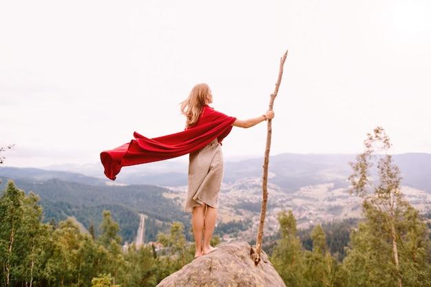 Mujer desconocida en vestido y capa roja de pie sobre piedra en la cima de la montaña