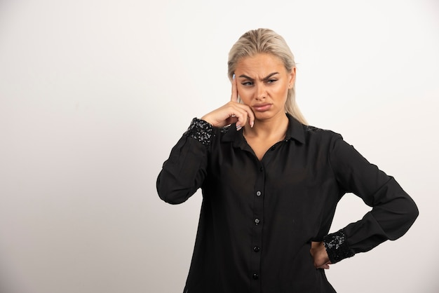 Mujer descontenta en camisa negra posando sobre fondo blanco. foto de alta calidad