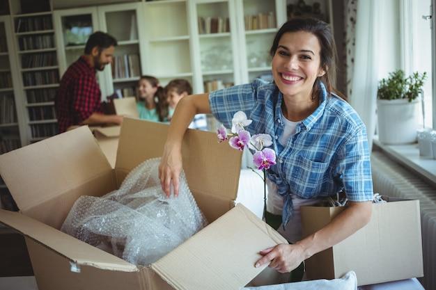 Mujer desempacando cajas de cartón mientras la familia de pie en el fondo