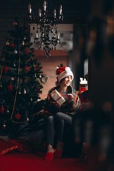 Mujer desempaquetando regalos por arbol de navidad