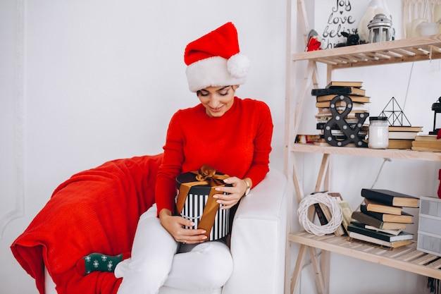 Mujer desempaquetando regalos en navidad