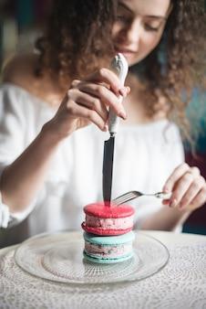 Mujer desenfocada insertando el cuchillo afilado y el tenedor sobre el sándwich de helado rosa y azul