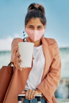 Mujer desenfocada con máscara médica con bebida y equipaje y en el aeropuerto durante la pandemia