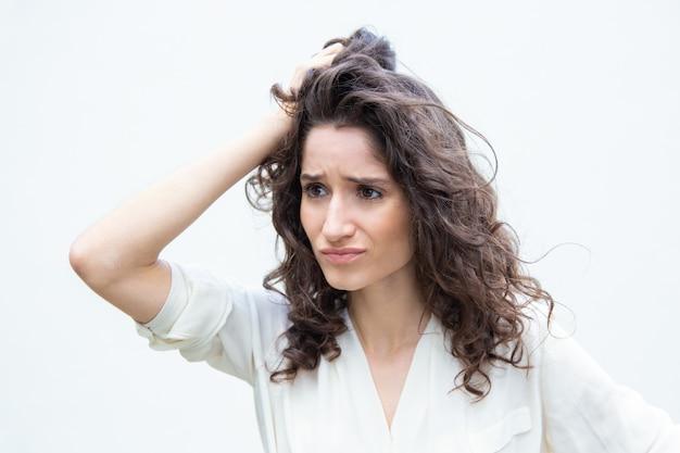 Mujer desesperada pensativa estresada rascándose la cabeza
