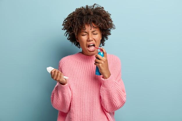 Mujer desesperada sufre de dolor en la garganta, se siente enferma y enferma, salpica spray en la boca, sostiene pañuelos de papel, vestida con un jersey de gran tamaño, aislada sobre una pared azul. tratamiento de la gripe o el resfriado
