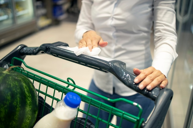 Mujer desinfecta el carrito de la compra con desinfectante antes de usarlo debido a la pandemia del virus corona