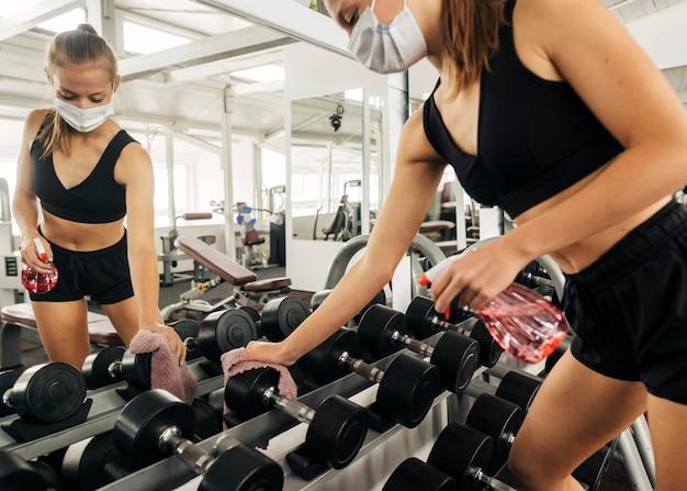 Mujer desinfectando equipos de gimnasio mientras usa una máscara protectora