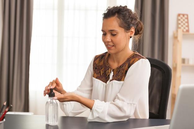 Mujer desinfectando las manos mientras trabaja desde la oficina en casa.