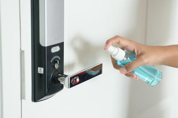 Mujer desinfectando el pomo de la puerta rociando un desinfectante azul de una botella, prevent covid19, corona virus.