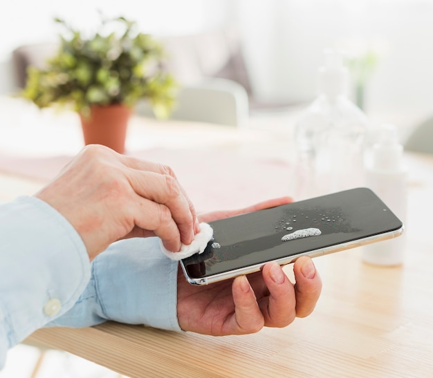 Mujer desinfectando su teléfono en casa
