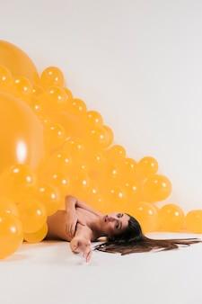 Mujer desnuda entra muchos globos amarillos