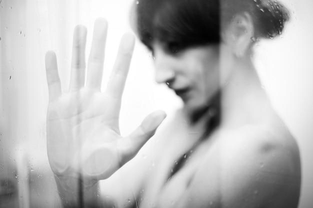 Mujer desnuda de pie detrás del vidrio y tomar una ducha