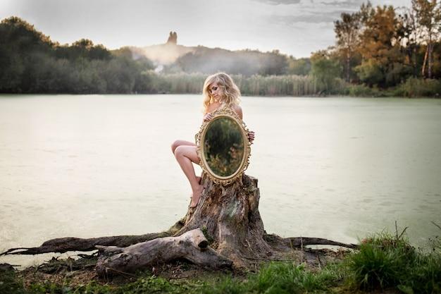 La mujer desnuda rubia sostiene un espejo que se sienta antes de un lago cubierto con la niebla