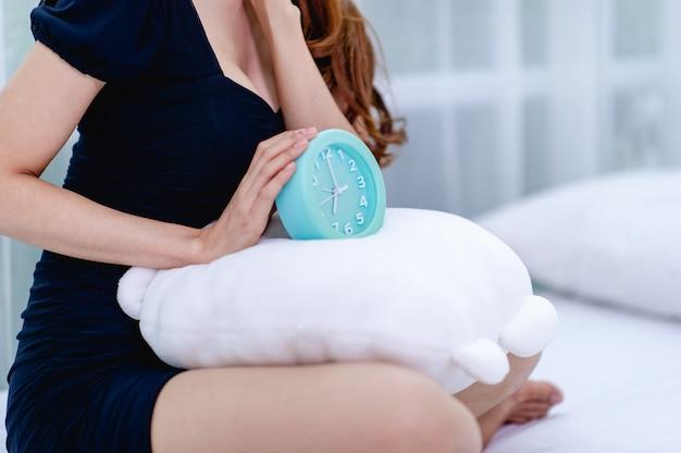 Mujer y despertador azul en el dormitorio concepto de relajación