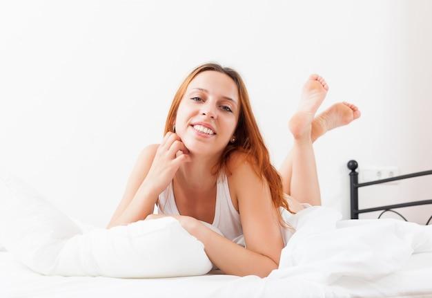La mujer está despertando lentamente en su cama