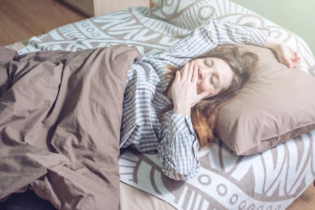 Mujer despertando en la mañana, acostada con sueño en la cama
