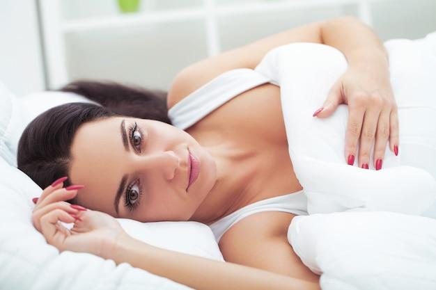 La mujer se despierta de un sueño prolongado en la cama bostezando y estirándose por la mañana en un día soleado