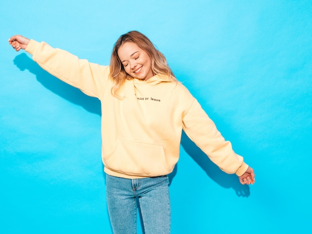 Mujer despreocupada atractiva que presenta cerca de la pared azul. modelo positivo divirtiéndose. levantando sus manos