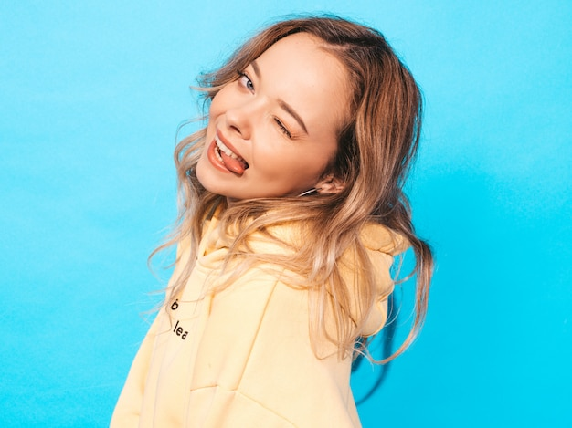 Mujer despreocupada atractiva que presenta cerca de la pared azul. modelo positivo divirtiéndose muestra lengua y guiños