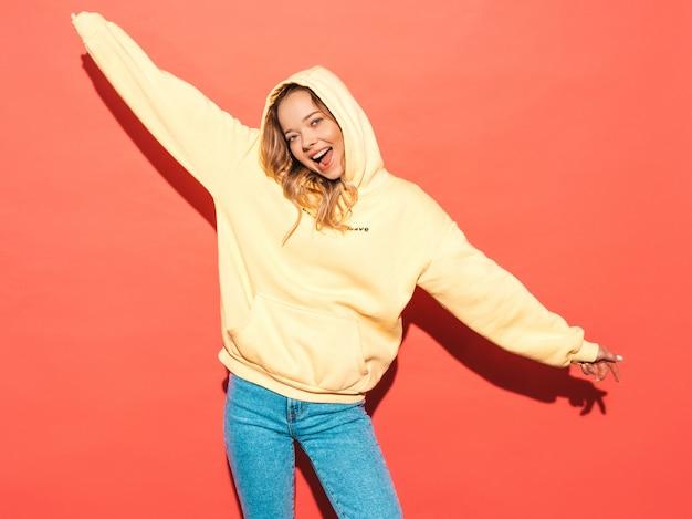 Mujer despreocupada atractiva que presenta cerca de la pared rosada. modelo positivo divirtiéndose. levantando sus manos