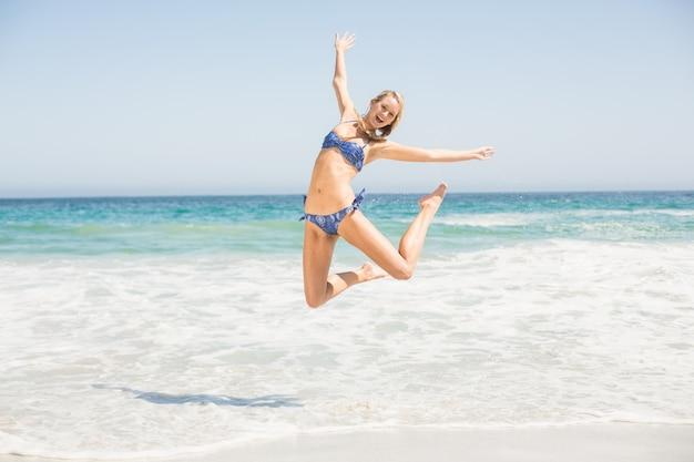 Mujer despreocupada en bikini saltando en la playa