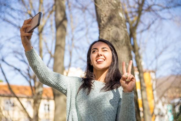 Mujer despreocupada haciendo muecas y tomando fotos selfie al aire libre