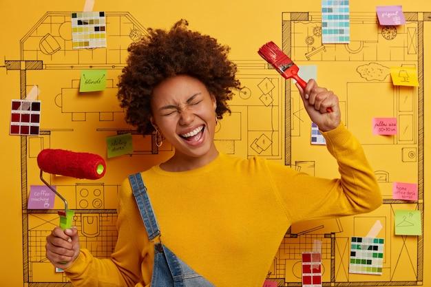 Mujer despreocupada con peinado afro sostiene herramientas de pintura, restaura paredes en casa