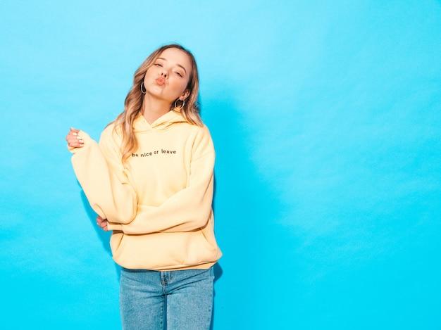 Mujer despreocupada posando junto a la pared azul en studio