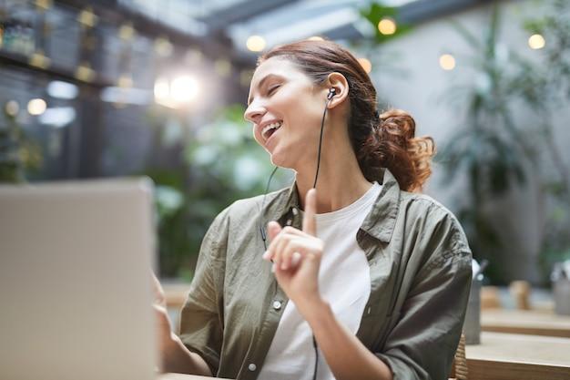 Mujer despreocupada que trabaja en el café al aire libre