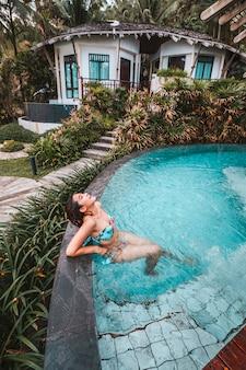 Mujer despreocupada relajación en piscina concepto de vacaciones de verano