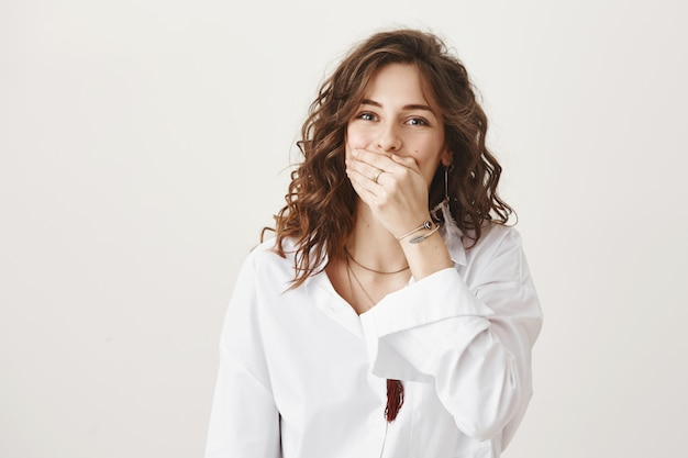 Mujer despreocupada riendo y tapándose la boca con la mano