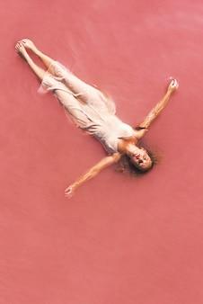 Mujer despreocupada de vacaciones deleitándose en el agua rosa del lago