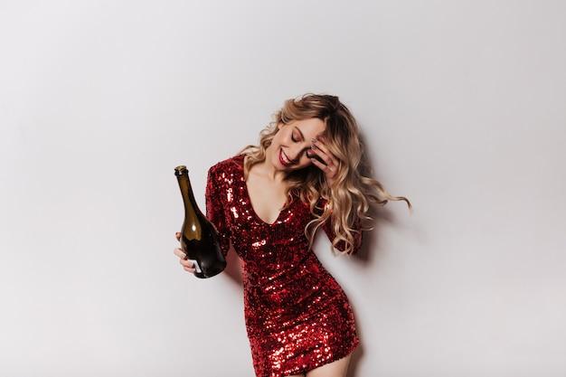 Mujer despreocupada en vestido corto bailando en la fiesta