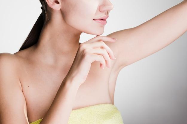 Mujer después de la ducha cuida la piel de las axilas